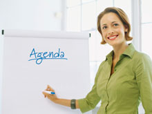 Leader pointing to agenda on flip chart