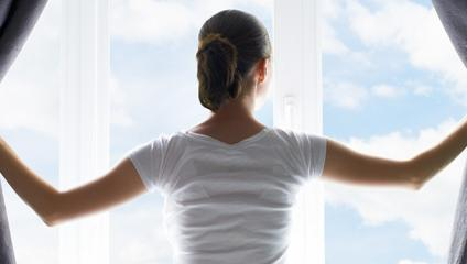 start early - woman opening curtains on morning sky