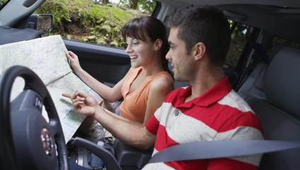 Man and a woman looking at a map in a car