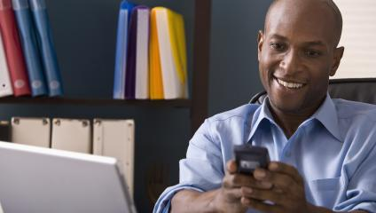 Man smiling while reading smart phone