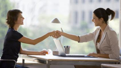 Two female employees shaking hands over a desk preparing for an interview