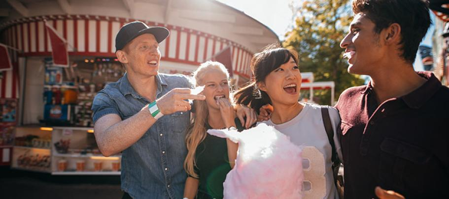 Friends on a boardwalk eating cotton candy