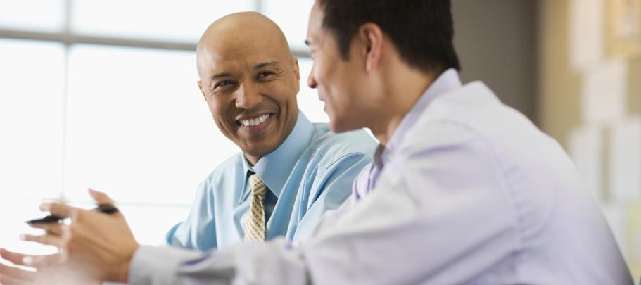 Two happy male employees talking at a table