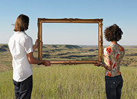 Two people holding a picture frame in front of grass and sky