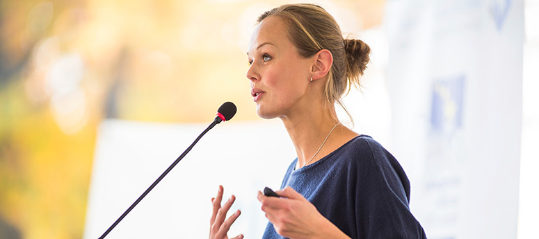 Female business leader speaking at a podium