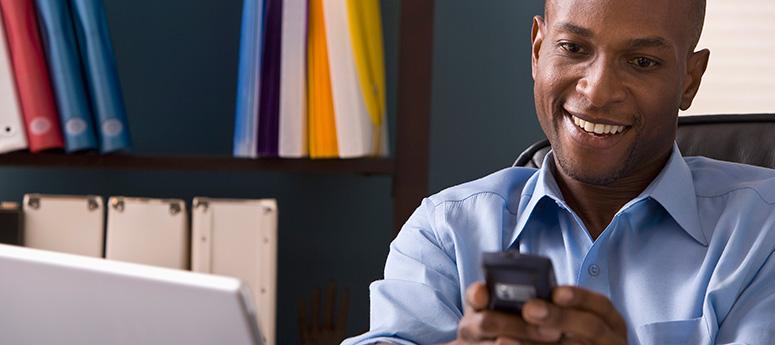 Man smiling while reading smart phone
