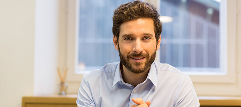 Male employee with beard looking at camera with hands folded - real person employee profile to personalize HR communication