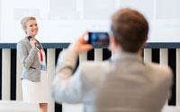 Leader at event taking a photo of speaker for social media post
