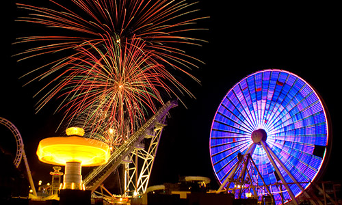 Neon ferris wheel and fireworks